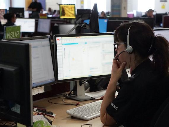 A police call handler talks into a telephone headset