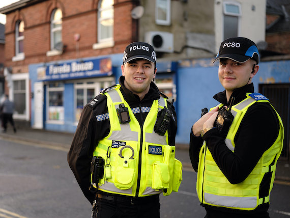A police officer and a PCSO stand in a town centre.