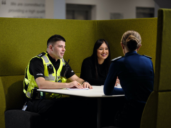 Two police officers and a staff member sit in a meeting