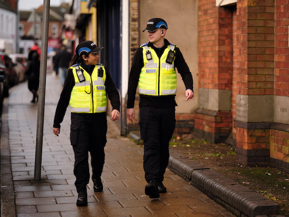 Two police officers walk down a busy street