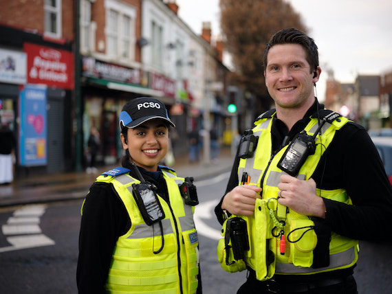 Two police officers smile standing in a town centre.