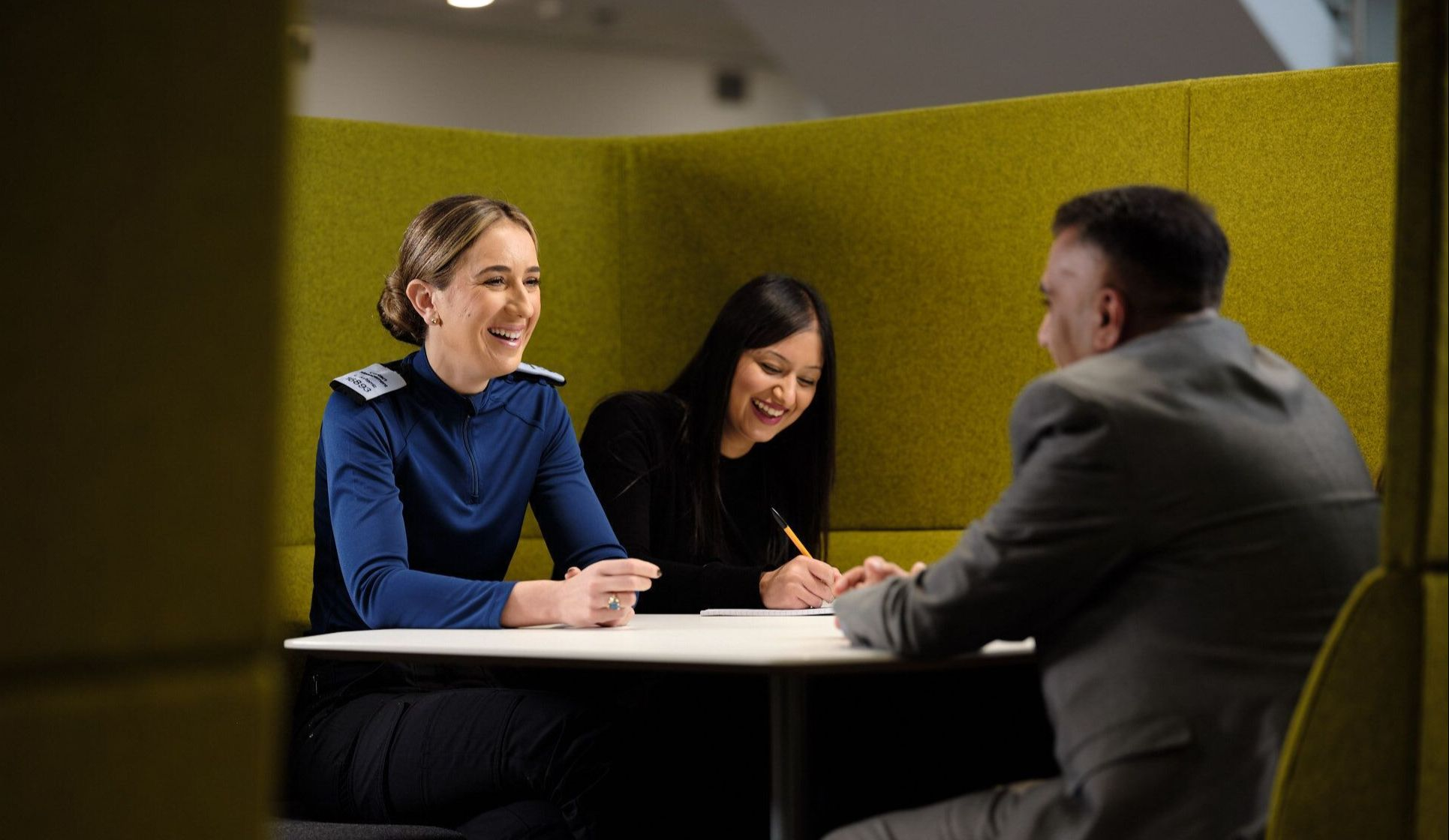A police officer laughs in a meeting with two staff members
