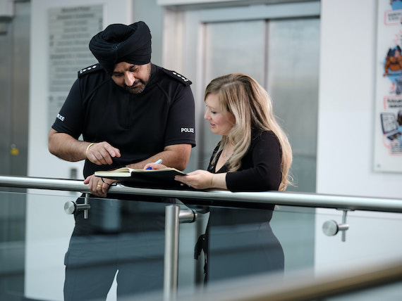 A staff member shows a notebook to a police officer.
