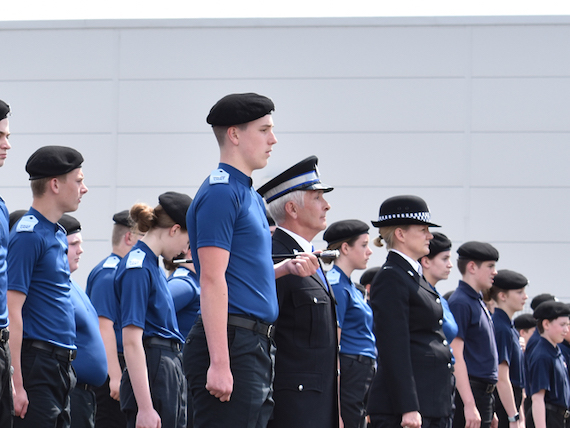 A group of uniformed cadets stand in lines