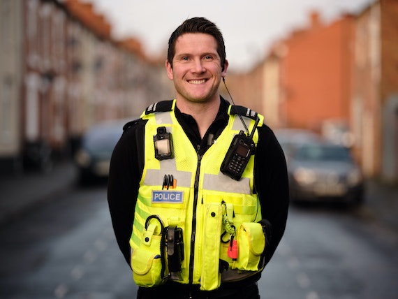 Derbyshire Constabulary Jobs | Careers Website | White Male Police Officer in Front of Row of Houses Image 3.jpg