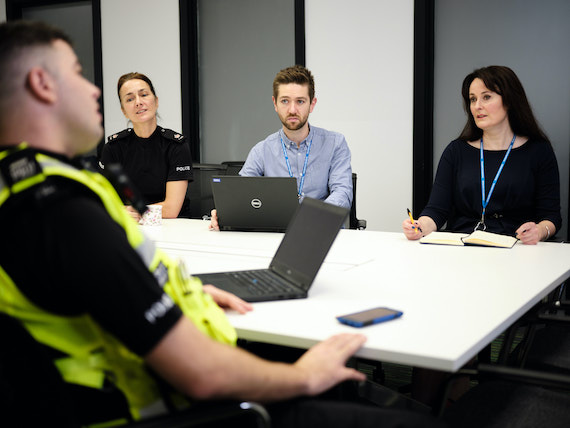 Two police officers sit in a meeting with two members of police staff.
