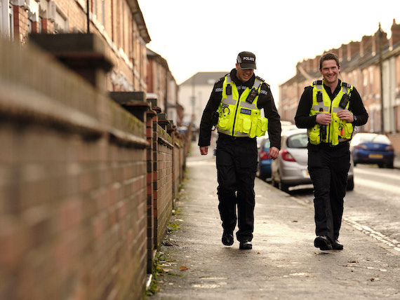 Two police officers walking down a Derby street