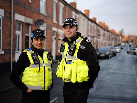 Two police officers stand in front of a row of houses