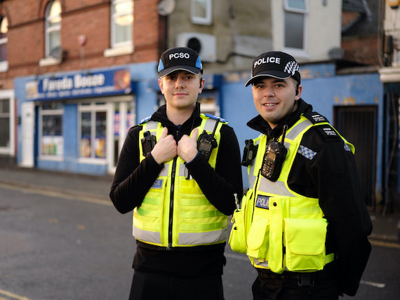 Two police officers stood in a town centre