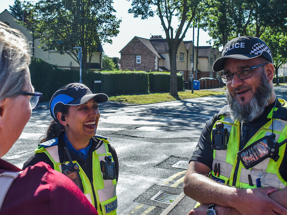 Two police officers speak to a member of the public