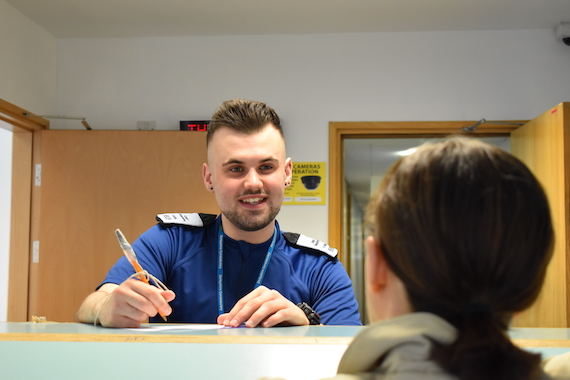 An officer talks to a member of public at a police station reception